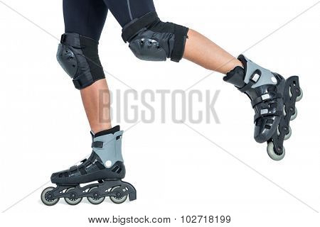 Low section of woman inline skating against white background