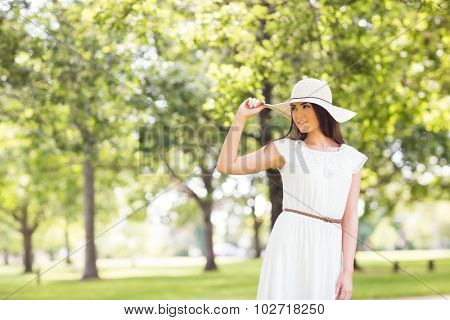 Confident young woman holding sun hat while standing on grassland in park