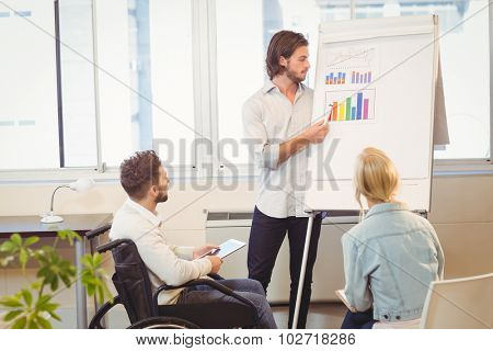 Businessman explaining multi colored graph on whiteboard while colleagues looking at it in meeting room in creative office