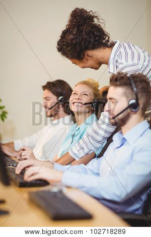 Businesswoman interacting happy female employee in call center