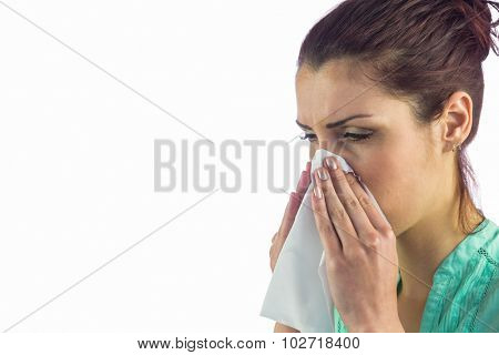 Close-up of sneezing woman with tissue on mouth against white background
