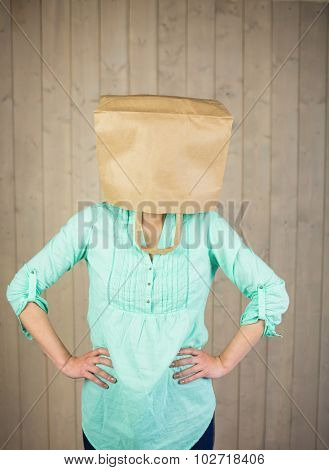 Woman with hands on hip and covering head with brown paper bag while standing against wall