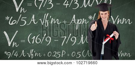 Teenage Girl Celebrating Graduation with thumbs up against green chalkboard