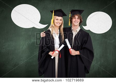 Two students in graduate robe shoulder to shoulder against green chalkboard