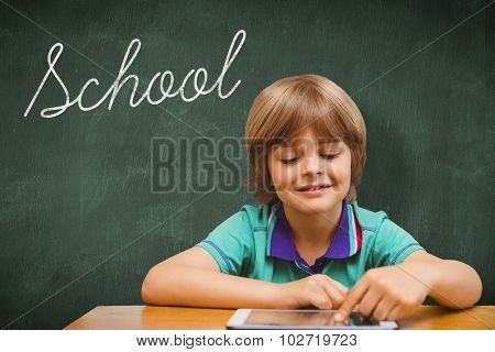 The word school and pupil using tablet pc against green chalkboard