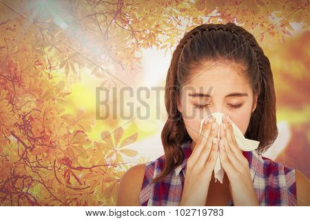 Close-up of sick woman sneezing in a tissue against autumn scene