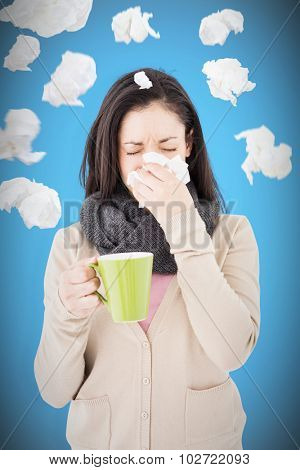 Sick woman blowing her nose while holding a green mug against blue background with vignette