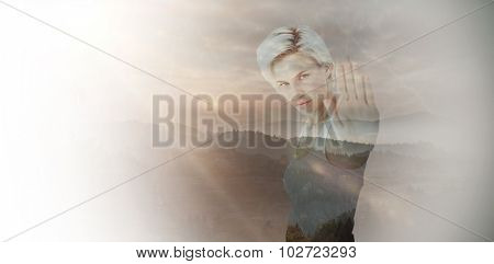 Angry pretty blonde showing her hand against trees and mountain range against cloudy sky