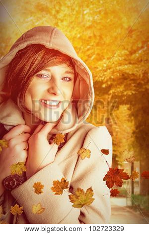 Portrait of smiling woman wearing winter coat against autumn scene