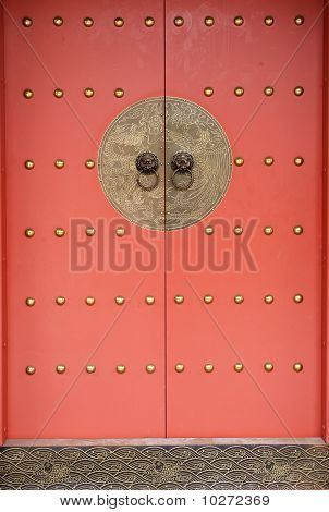 A Chinese Traditional Red Door With Coppery Decoration