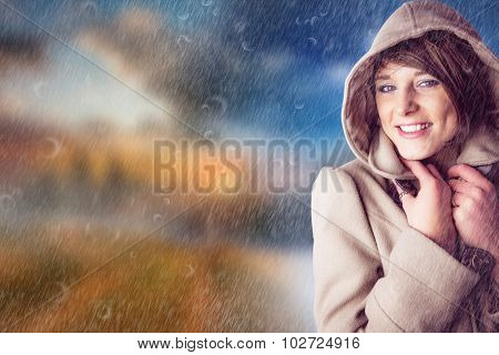 Portrait of smiling woman wearing winter coat against autumn changing to winter
