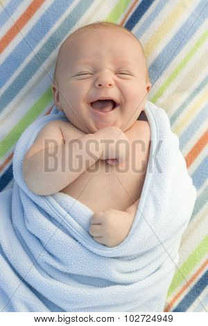 Beautiful Laughing Baby Boy Wrapped in His Blanket.