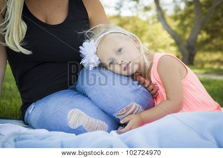 Beautiful Young Blue Eyed Girl Resting on Her Mommy's Lap Outside At the Park.
