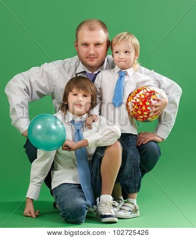 Portrait Of Happy Father And Two Sons On A Green Background