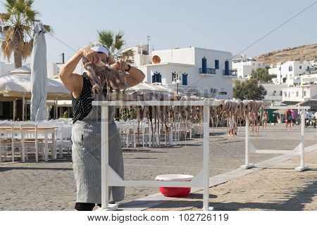 Athens, Greece 15 August 2015. Old lady hanging an octopus to dry in the sun at Paros island in Gree