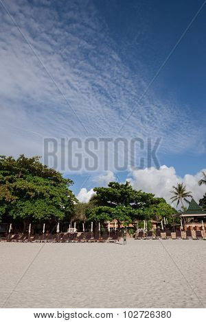 Beach on tropical island. Clear sand, clouds.