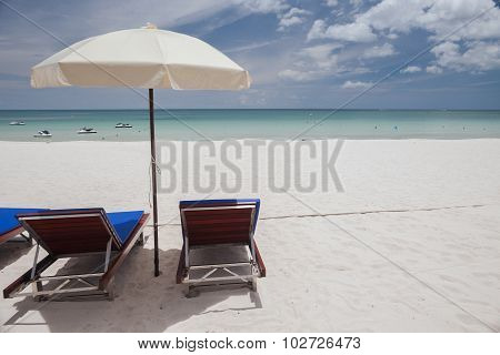 Beach on tropical island. Clear blue water, sand, clouds.
