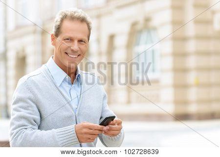 Smiling man holding mobile phone