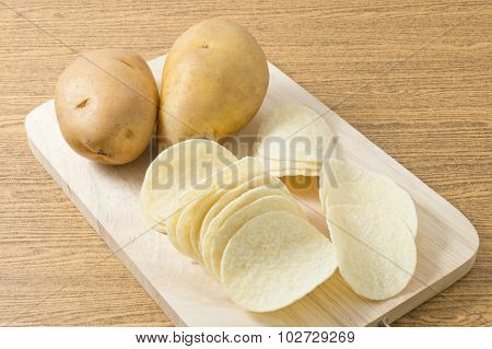 Potato And Potato Chips On Cutting Board