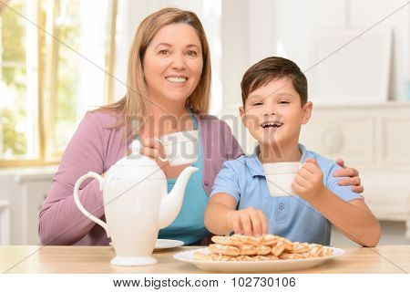 Cheerful boy sitting in the kitchen