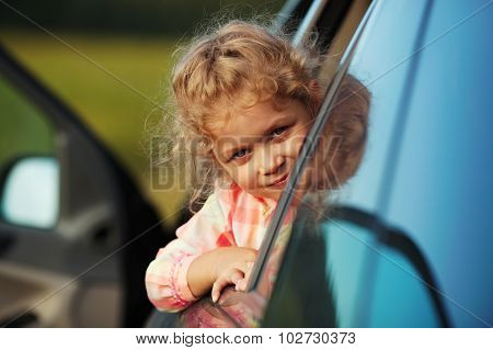 Little Girl Looks Out The Car Window