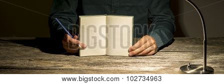 Front View Of Male Student Holding His Blank Notebook With Squared Sheets Opened Towards You