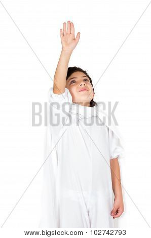 Small boy wearing all white clothing and dark hair holding right arm up to the sky as in flying