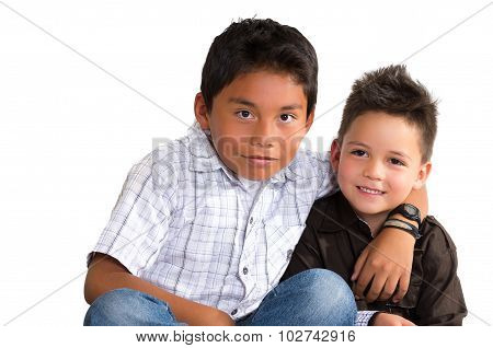 Two small hispanic boys sitting next to each other holding arms around like friends, white backgroun
