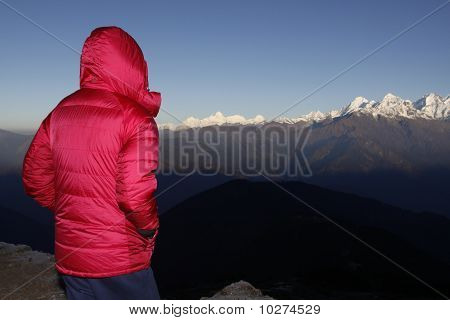 Girl watching sunrise on the mountains, Nepal.