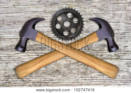 2 hammers, gear wheel on a wooden background