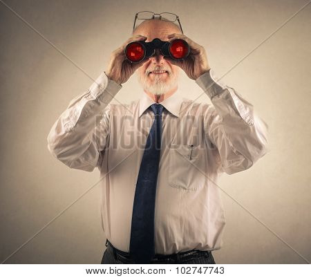 Businessman looking through a binoculars