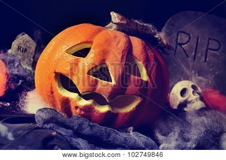 closeup of a Halloween jack-o-lantern in a dismal scenery, with skulls and gravestones