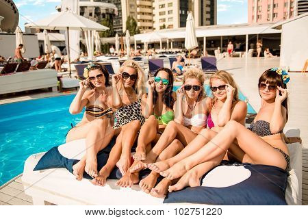 Happy Girls On The Beach. Beautiful Girlfriends Lying On A Lounger By The Pool And Show Their Legs A