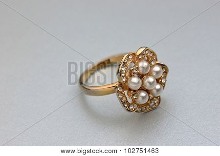 Close up of a women's ring. Golden ring with embedded pearls on top.