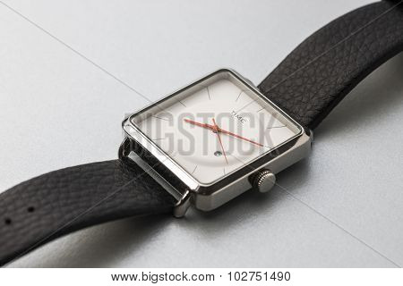 An elegant gent's wrist watch with white dial. Close up of watch with open strap.