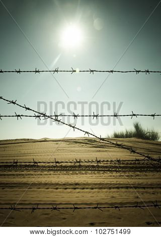 Metal barbed wire fence in the desert against bright sun in the sky.