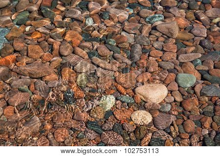 Colorful, Smooth Stones Lie Under Ripples Of Water Near The Shoreline Of Lake Superior In Minnesota