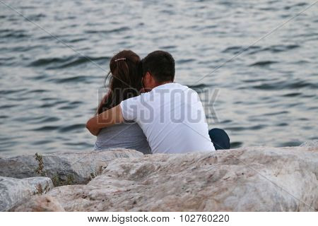 Couple sitting near the sea.