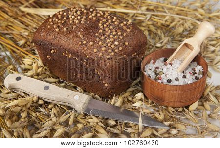 Loaf of homemade bread with black mustard seeds on a table with spikelets of rye and oat sand salt shaker salt and knife.
