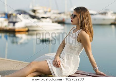 Young Woman Sitting By The Marina