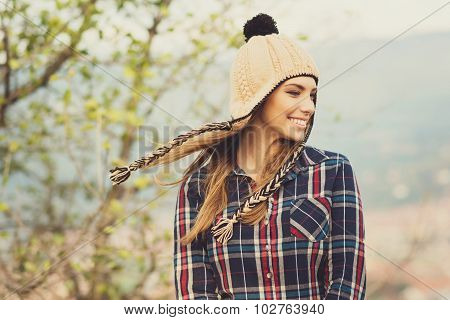 Young woman in plaid shirt and knitted hat in autumn