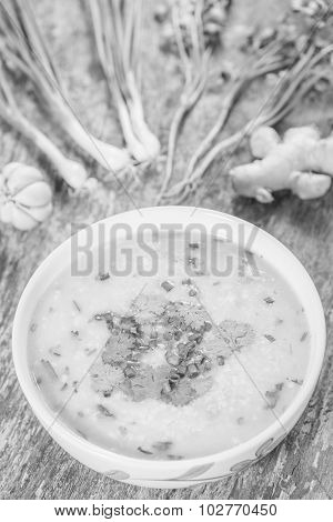 Traditiona Porridge Rice Gruel In Bowl On Wooden Background , Black And White