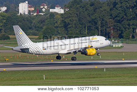 ZURICH - JULY 18: Airbus A-320 Vueling landing in Zurich after short haul flight on July 18, 2015 in Zurich, Switzerland. Zurich airport is home for Swiss Air and one of biggest european hubs.