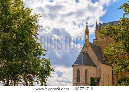 Old Gothic Chapel With Trees And Cloudy Sky