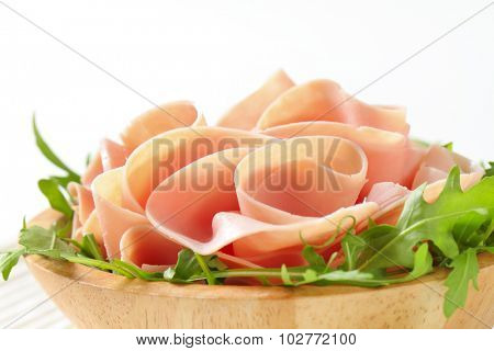 detail of fresh arugula salad with sliced ham in wooden bowl