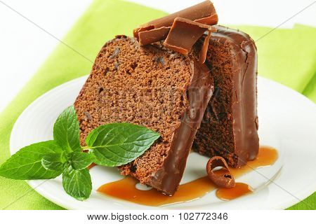 close up of chocolate cake slices with mint, chocolate shavings and caramel topping on white plate and green napkin