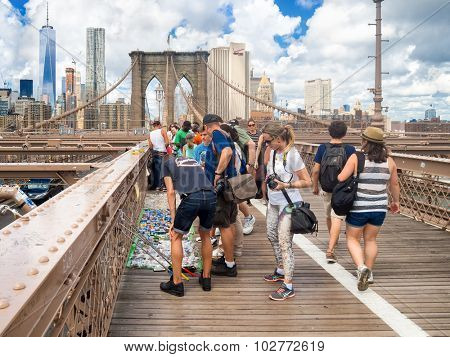 NEW YORK,USA - AUGUST 20,2015 : Tourists buying souvenirs from street vendors at the Brooklyn Bridge in New York