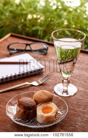 Cup Cake With A Delicious Glass Of Cold Water. Wooden Background.