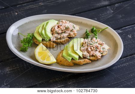 Sandwich With Avocado, Salmon And Whole Wheat Bread On An Oval Plate On A Dark Wooden Surface, A Hea