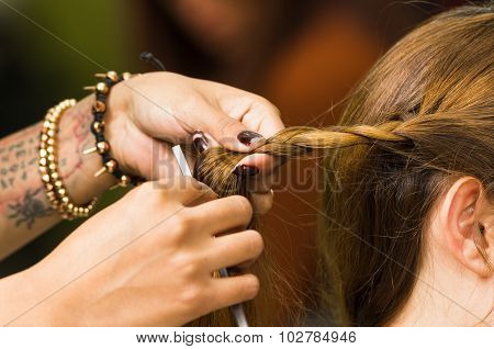 Closeup stylist hands working with brunette hair making a twist
